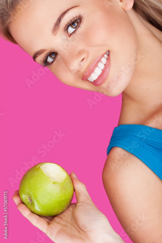 Smiling woman holding a bitten apple