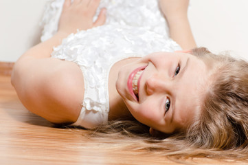 Happy kid lying on floor smiling and looking into camera