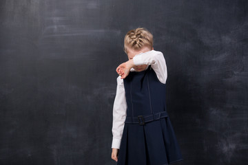 Offended schoolgirl stands at the blackboard