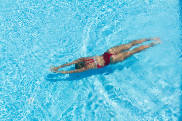 Woman with swimsuit swimming on a blue water pool