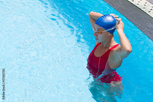 Young woman in goggles in swimming pool