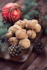 Walnuts, fir-cones and xmas ball over rustic wooden background