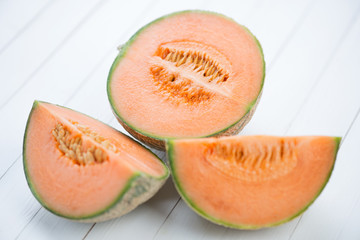Sliced cantaloupe melon on white wooden boards, close-up