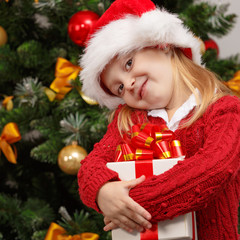Happy little girl  with gift box near the Christmas tree