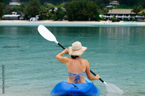 Young caucasian woman kayaking over turquoise water