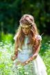 Girl in white dress picking flowers.