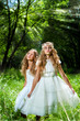 Litte princesses wearing white dresses in woods.