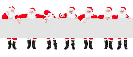Group Of Santa Claus With Poster Banner