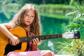 Young guitar student playing at lake.