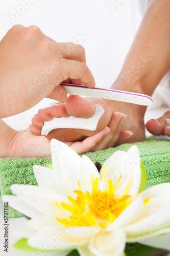 Manicurist Filing A Female Nails