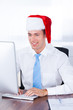 Young Businessman Wearing Santa Hat Using Computer In Office