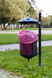 Trash basket with pink plastic bag, standing in park.