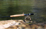 Fly fishing rod on the stone by the river