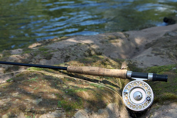 Flyfishing rod on the stone by the river