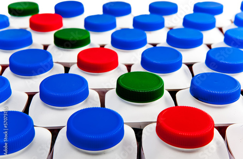 dairy products bottles stand in rows, bright covers