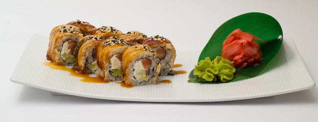Canada sushi roll on white plate with ginger and wasabi