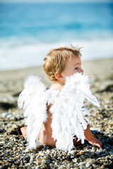Cute boy sitting on the beach