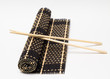 Chopsticks on bamboo mat and white background