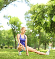 Young blond female exercising in a park on a sunny day