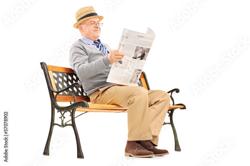 Senior gentleman reading newspaper and sitting on a bench