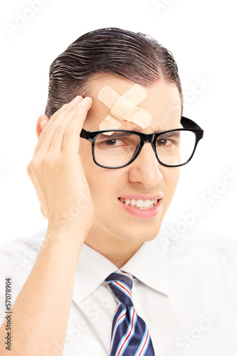 Serious young man with plaster on his forehead having a headache