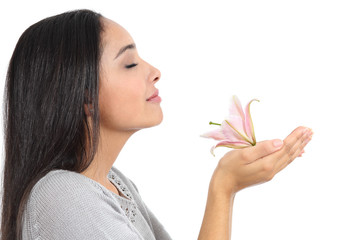 Side view of an arab woman smelling a flower