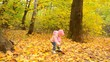 Cute Little Baby Girl is Playing with Yellow Leafs in Autumn Col