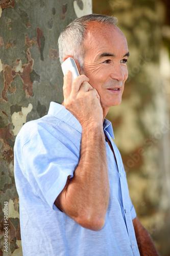 senior citizen making a call outdoors