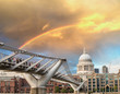 Rainbow over Millennium Bridge in London. St Paul Cathedral on b