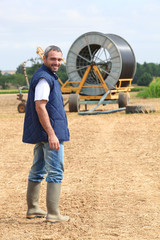 Famer stood in field machinery in background
