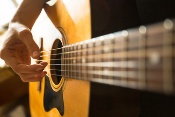 Close-up female hand playing on acoustic guitar..