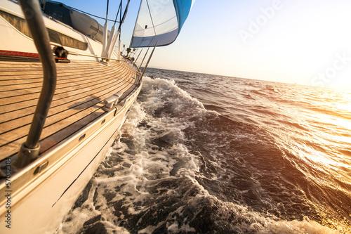 Yacht sailing towards the sunset. Luxury yachts. - 57082384