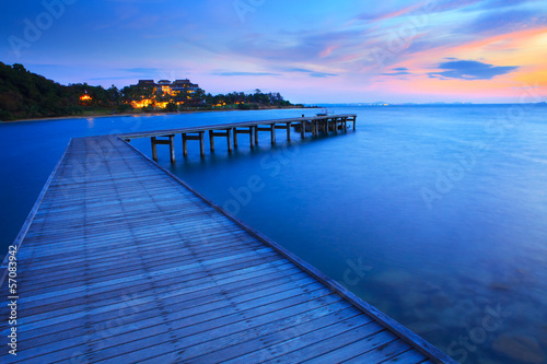 wood bridge pier into blue sea at morning time