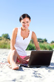 Attractive woman with laptop working on the beach