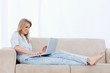 A woman is lying on a couch typing on her laptop