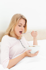 Woman in bed with her mouth open about to eat a spoon of cereal