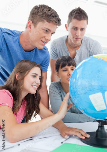 Close up of four people looking at the globe of the world