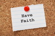 Have Faith on a paper note pinned to a cork notice board
