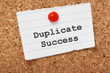 Duplicate Success on a paper note pinned to a cork board