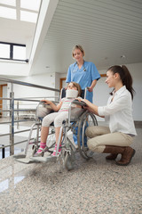 Mother crouching next to her child in wheelchair with nurse push