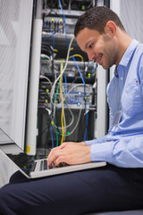 Man using laptop in front of servers