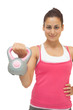 Smiling sporty brunette holding grey and pink kettlebell