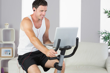 Sporty man with earphones exercising on bike and holding laptop