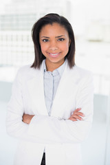 Smiling young dark haired businesswoman posing with arms crossed