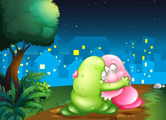 A pink and a green couple monsters hugging each other at the pat