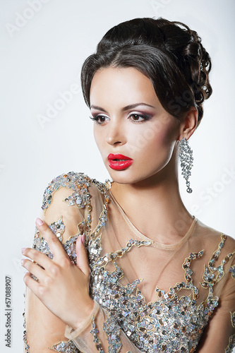 Elegance. Luxurious Woman in Dress with Sequins and Jewels