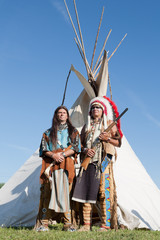 Two North American Indians stand near a wigwam