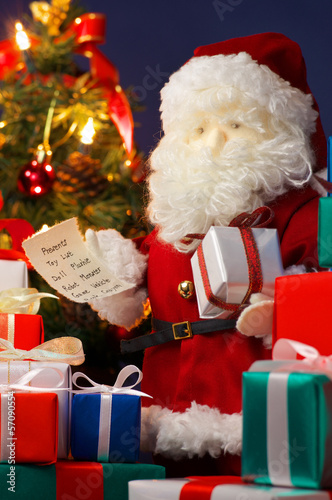 Santa Claus preparing Christmas presents. (vertical)
