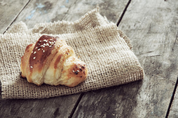 Croissant over wooden background