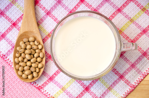 Soybean on wooden spoon and soy milk in a glass.